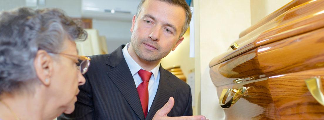 hombre mostrando a una mujer un ataúd