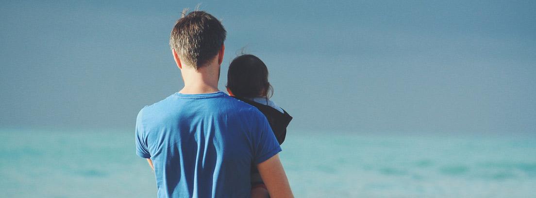 Hombre de espaldas con un niño en brazos en una playa