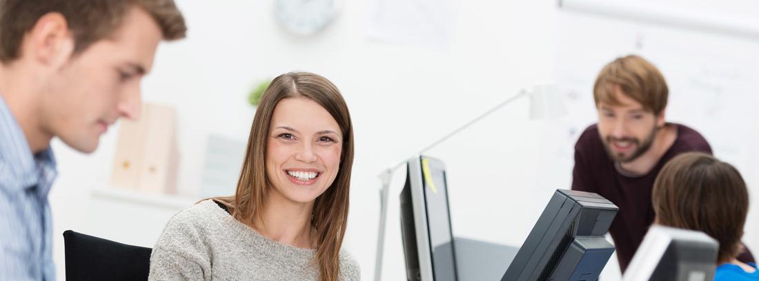 Mujer sonriente rodeada de más personas trabajando en una oficina como las nuevas del Servef