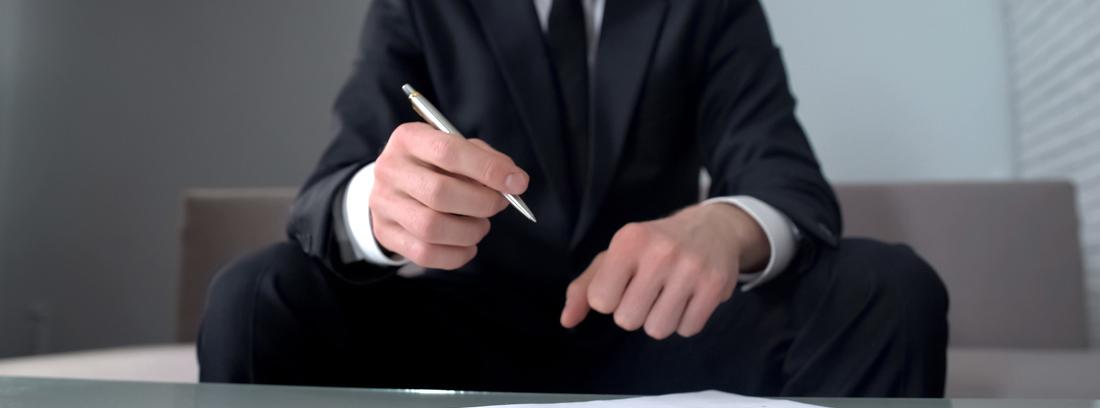 Hombre con traje firmando los papeles de un aval bancario