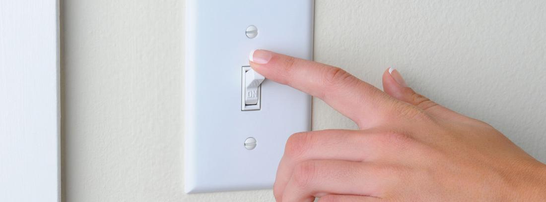 mano pulsando un interruptor de la luz