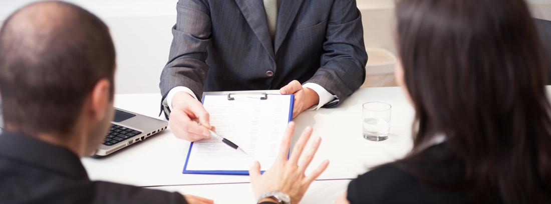 hombre mostrando un contrato para firmar a una pareja