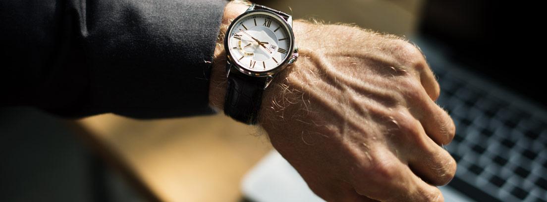 Brazo de hombre con reloj delante de un ordenador
