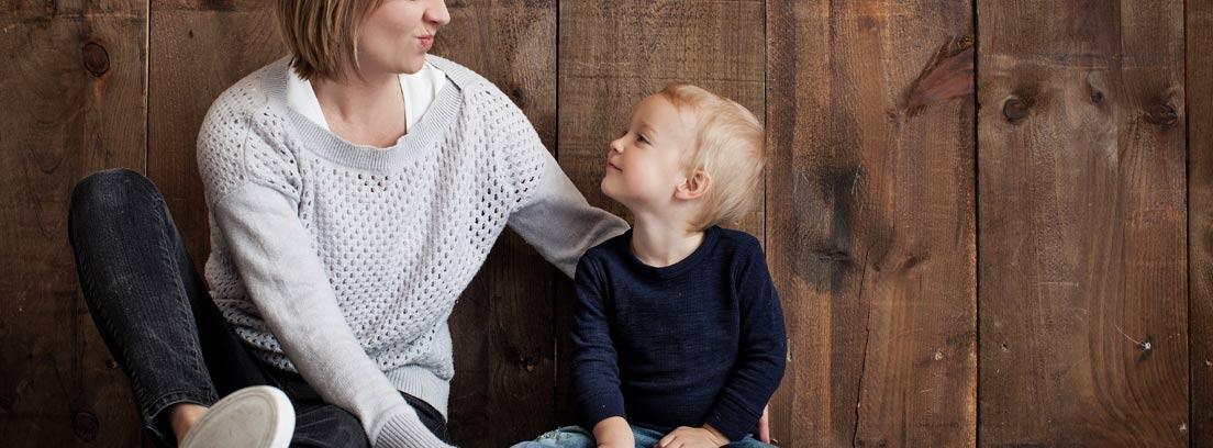 Mujer sentada en el suelo al lado de un niño, disfrutando de la reducción de jornada laboral por cuidado de hijos