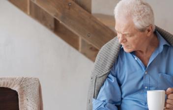 Hombre mirando una fotografía, a su lado una silla vacía con una taza