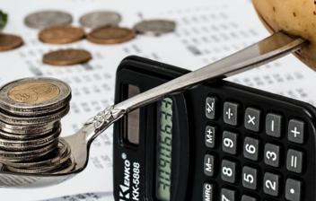 Monedas y patata sobre una cuchara en equilibrio sobre una calculadora