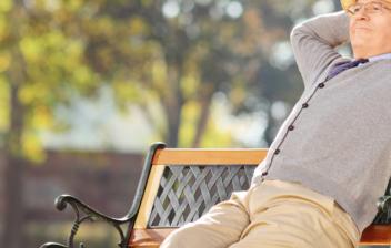 Hombre mayor sentado en un banco con actitud relajada