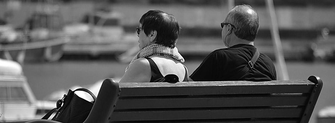 Dos personas sentadas de espaldas en un banco