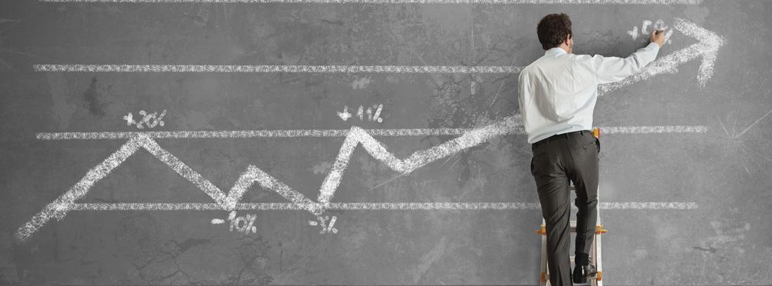 Hombre pintando sobre una pizarra una flecha de aumento de beneficios
