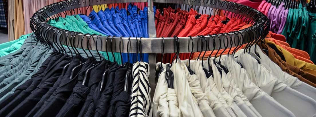 Varias camisetas colgadas en un perchero en una tienda de ropa