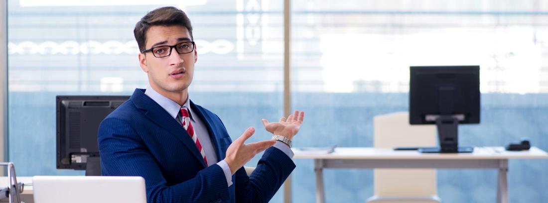 Hombre en una oficina señalando una mesa vacía