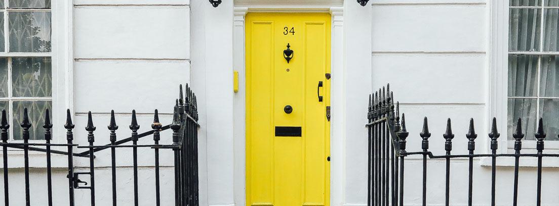 Entrada de una casa con una puerta amarilla y escalones