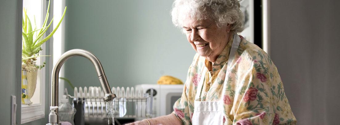 Mujer mayor lavando zanahorias en una cocina