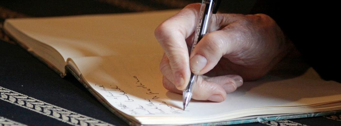 Mano con boli escribiendo en un cuaderno un testamento antes de los cambios en el impuesto de sucesiones en Andalucía