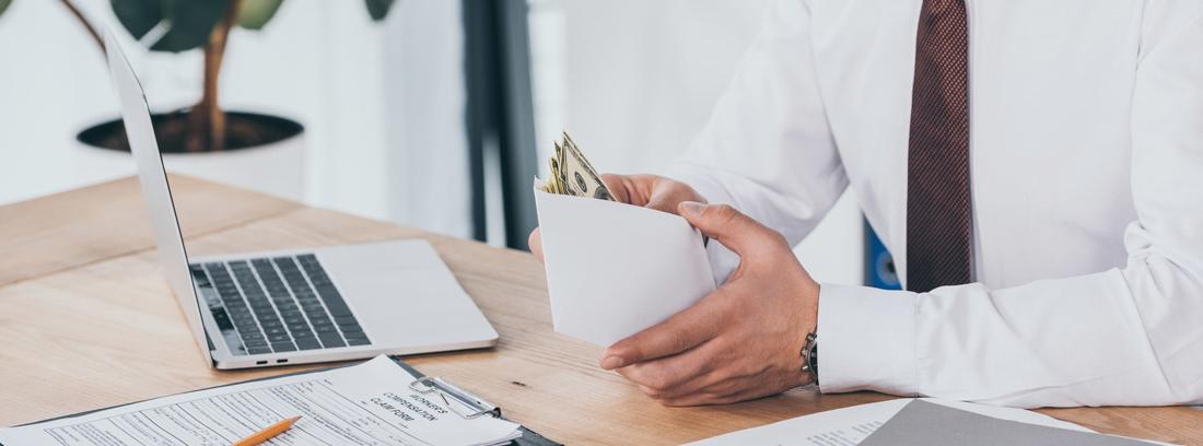 Hombre en su puesto de trabajo, delante de una mesa con un ordenador y unos papeles abriendo un sobre lleno de billetes