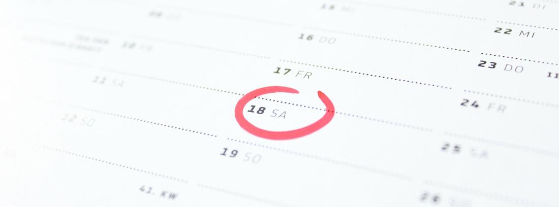 Hoja de calendario de papel con número rodeado en color rojo