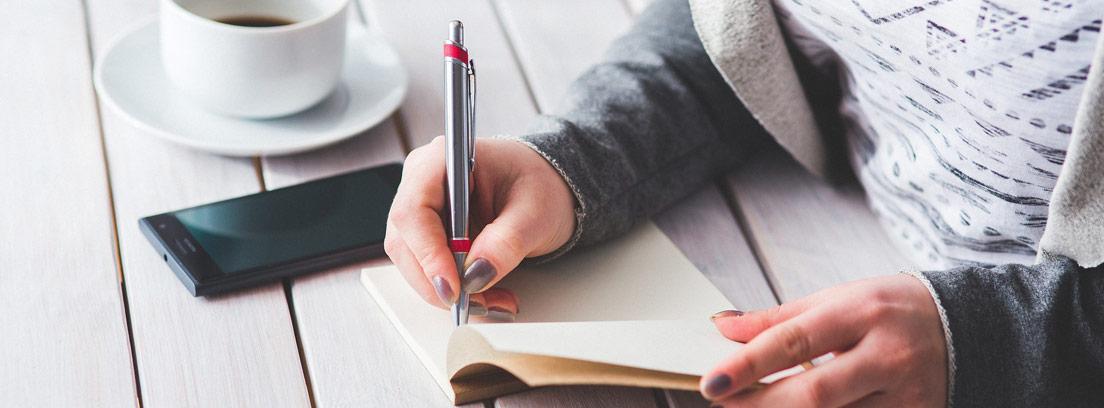 Mujer apunta en una agenda junto a un teléfono móvil y una taza