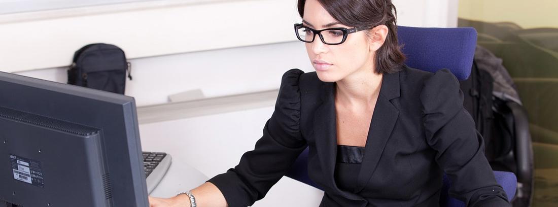 Mujer sentada delante de ordenador con agenda