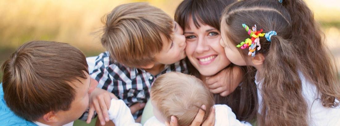 Familia numerosa con tres hijos dando besos a su madre