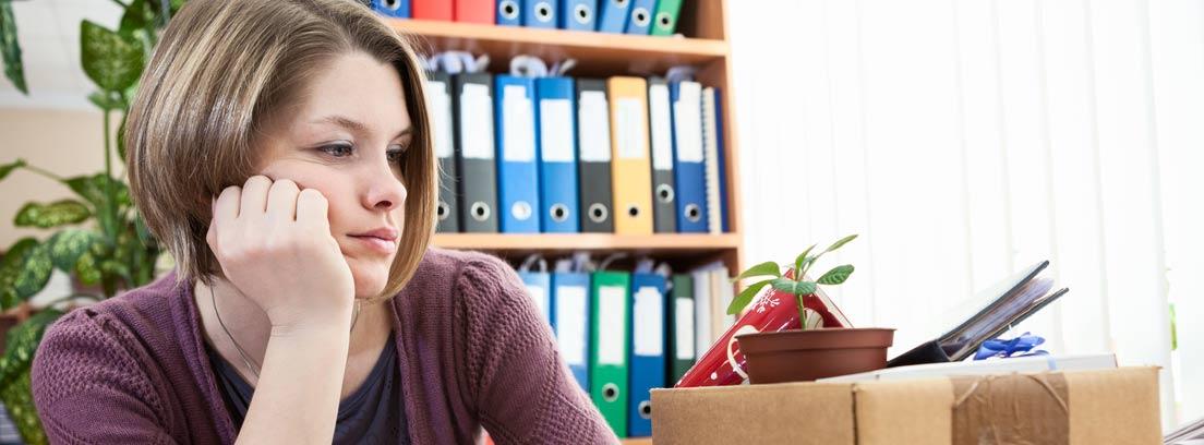 Mujer apesadumbrada observando una caja con sus cosas