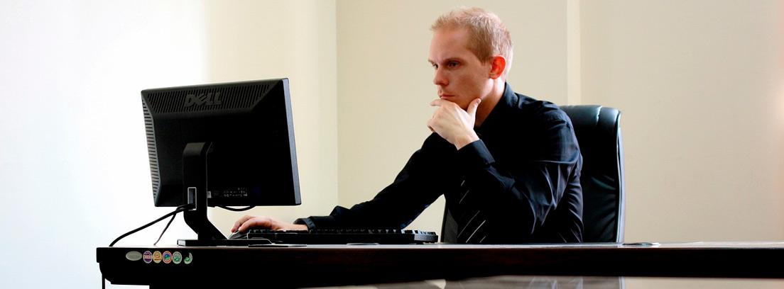 Hombre trajeado sentado frente a un ordenador