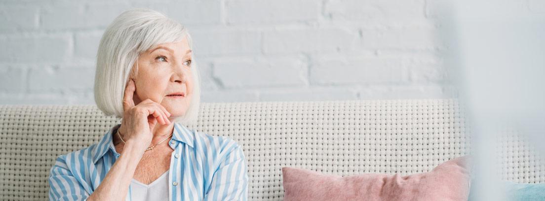 Mujer mayor sentada en un sofá pensando