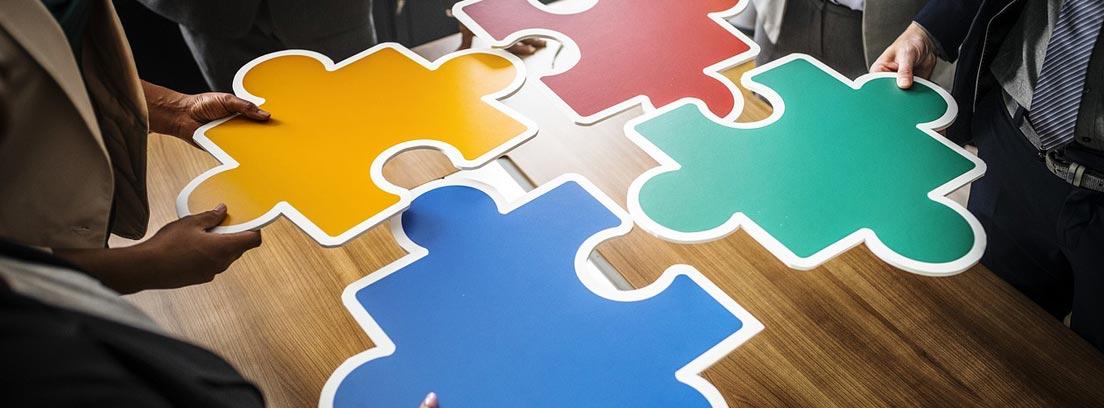Varias personas sujetan piezas grandes de puzle de colores