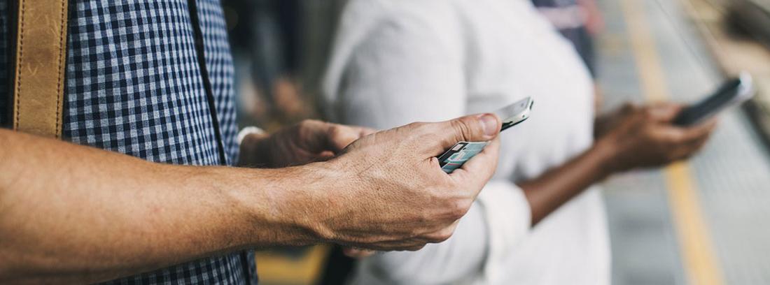 Dos personas mirando la pantalla de su teléfono en un andén