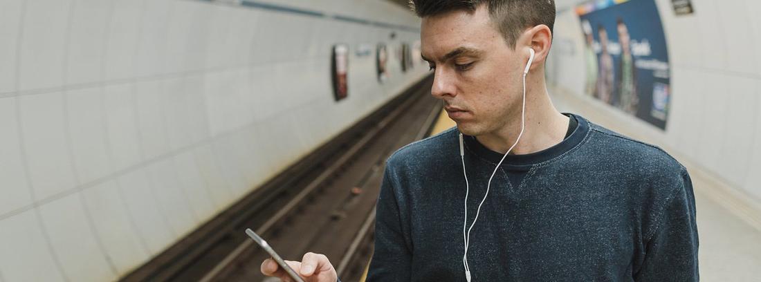 Hombre en una estación de metro mirando su móvil