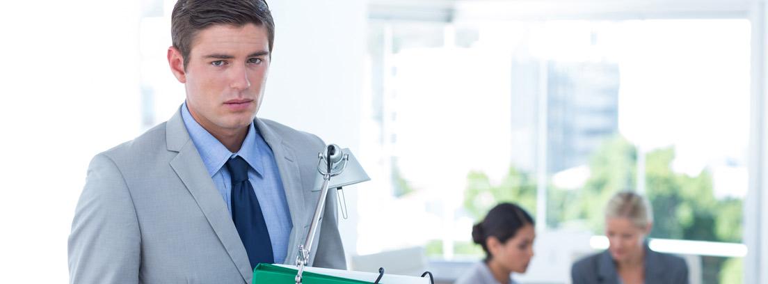 Hombre triste portando una caja con sus cosas saliendo de una oficina