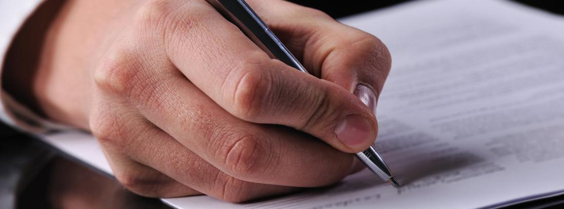 Hombre de traje firmando documentos