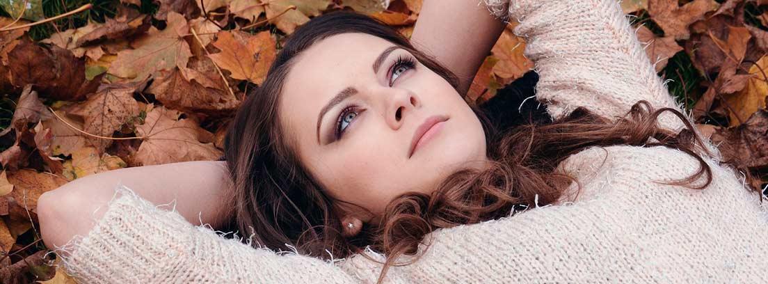 Mujer tumbada en el suelo sobre hojas