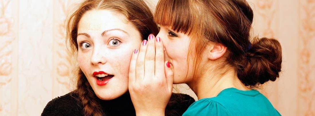 Una mujer contando un secreto al oído a otra mujer con gesto de sorpresa