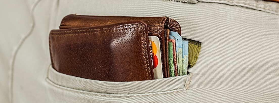 Vista parcial del bolsillo de un pantalón con una cartera repleta de billetes