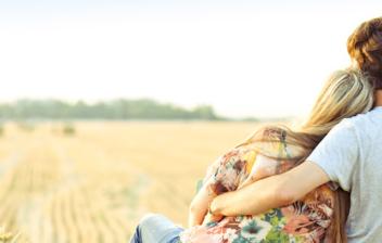 Hombre y mujer sentados de espaldas sobre una paca de heno mirado el horizonte