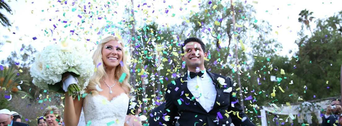 Confeti cayendo sobre pareja de recién casados sonrientes