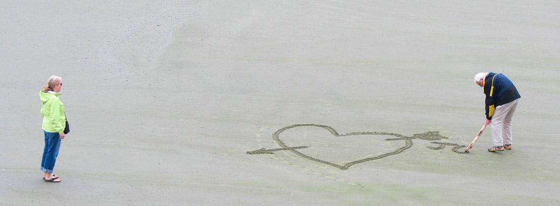 Mujer mira a hombre de pelo blanco que dibuja corazón en arena de la playa