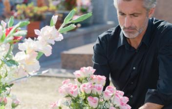 Hombre de pelo blanco y vestido de negro pone flores sobre una lápida