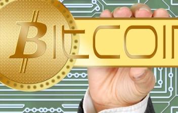 Mano sujetando una moneda con la palabra bitcoin