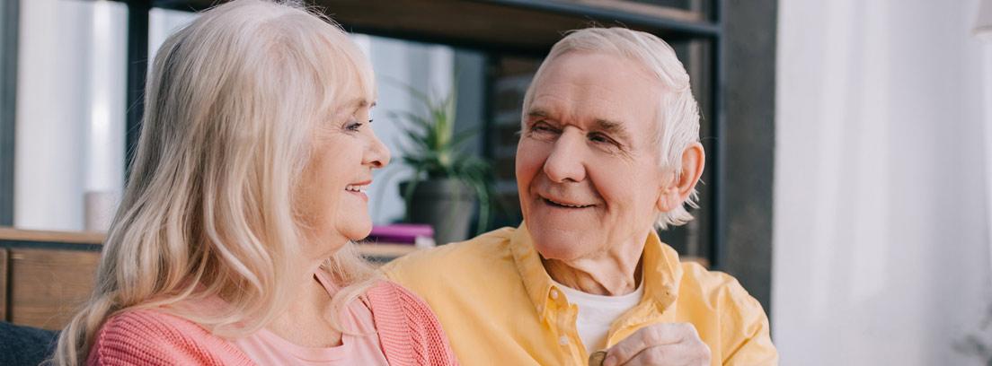 Dos jubilados poniendo dinero en una hucha con forma de cerdito