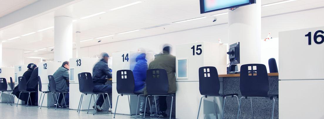 Varios puestos en una oficina pública con personas sentadas