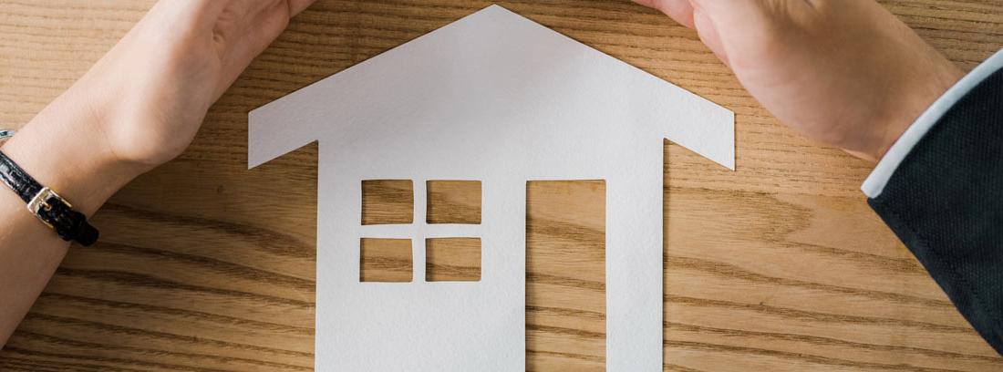 Manos protegiendo el dibujo de una casa en blanco
