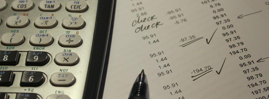 Hoja con apuntes de números junto a calculadora y bolígrafo