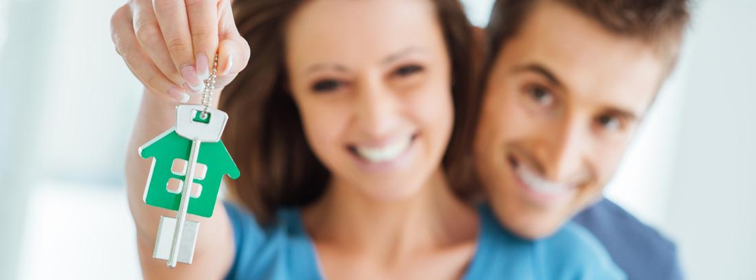Primer plano de un hombre y una mujer sonrientes sujetando unas llaves tras comprar casa