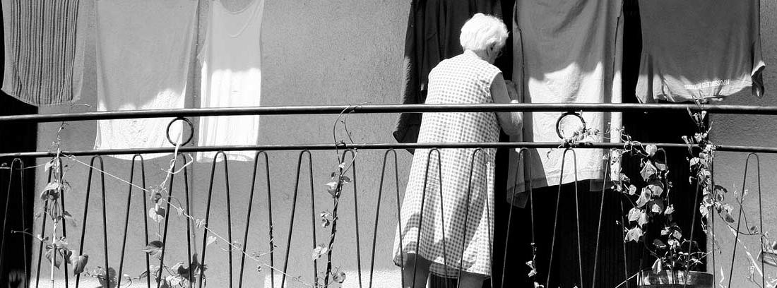 Mujer mayor en un balcón tendiendo la ropa