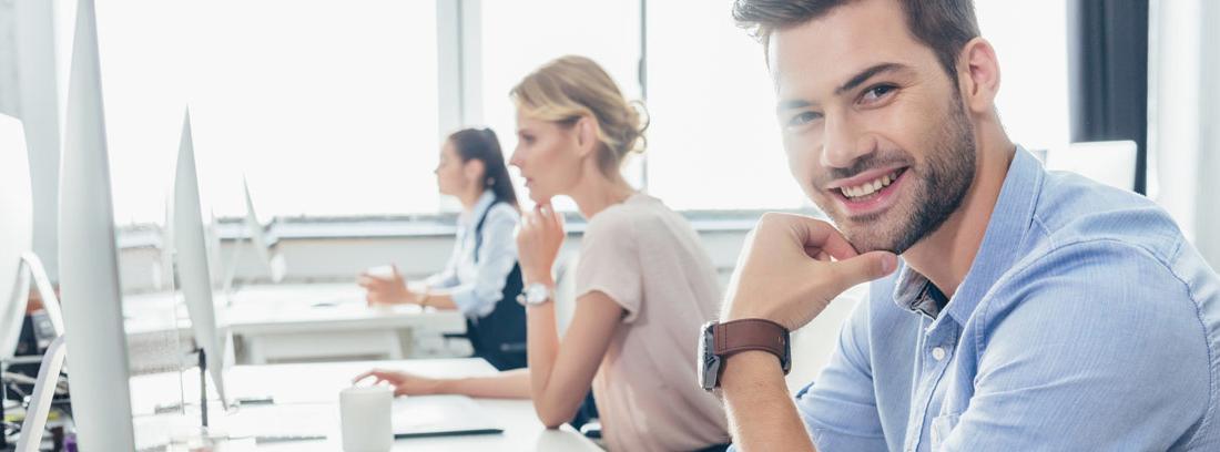 Varias personas sonrientes sentadas frente a un ordenador