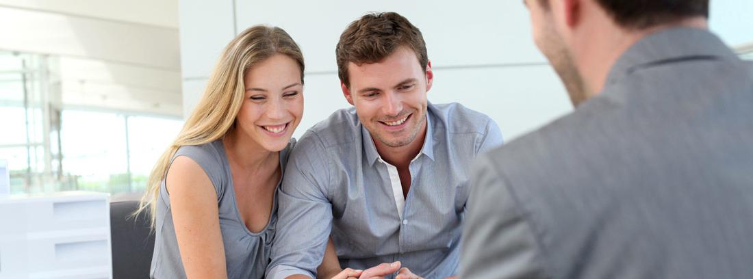 Hombre y mujer sentados en mesa con papeles frente a otra persona