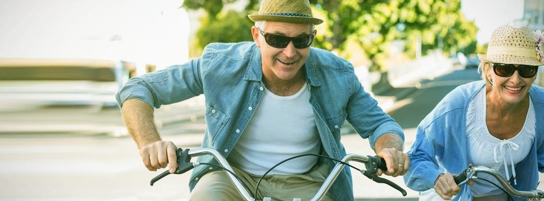 Dos personas mayores con sombrero y gafas de sol montando en bicicleta
