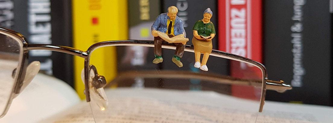 Dos figuritas de ancianos leyendo sobre unas gafas