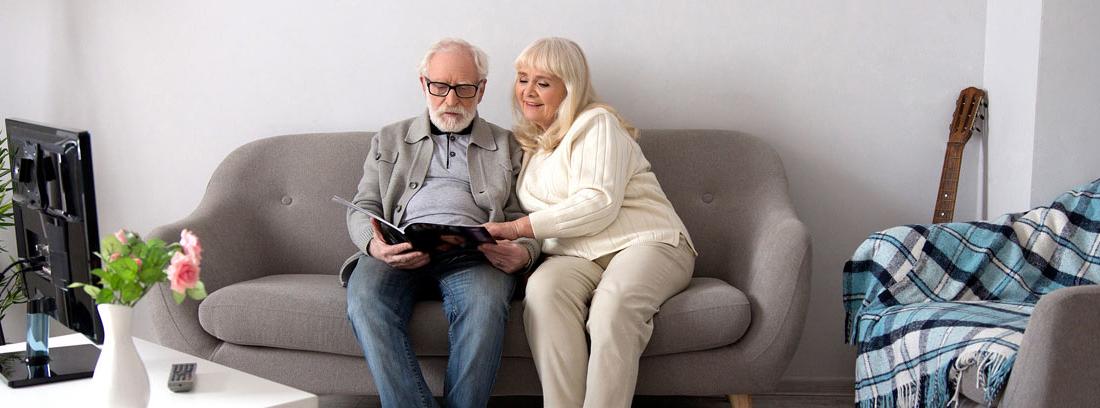 Pareja de ancianos sentados en un sofá leyendo un libro tras vender su casa en nuda propiedad